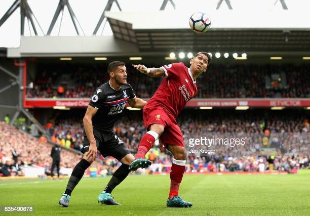 Roberto Firmino of Liverpool and Joel Ward of Crystal Palace battle for possession during the Premier League match between Liverpool and Crystal...