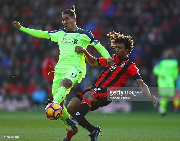 Roberto Firmino of Liverpool and Nathan Ake of AFC Bournemouth battle for the ball during the Premier League match between AFC Bournemouth and...