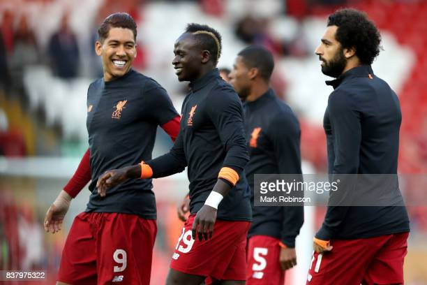 Roberto Firmino of Liverpool and Sadio Mane of Liverpool speak while warming up prior to the UEFA Champions League Qualifying PlayOffs round second...