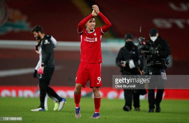 Roberto Firmino of Liverpool applauds the near 2000 crowd in the Kop after scoring a last minute winning goal during the Premier League match between...