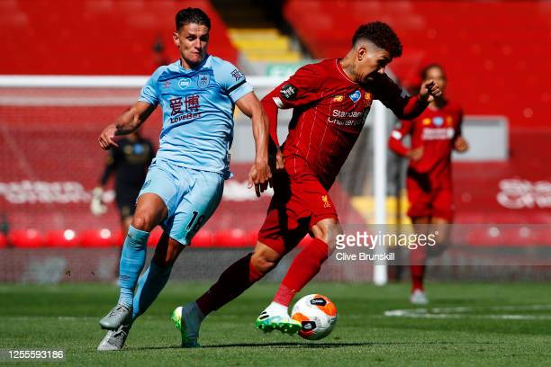 Roberto Firmino of Liverpool battles for possession with Ashley Westwood of Burnley during the Premier League match between Liverpool FC and Burnley...