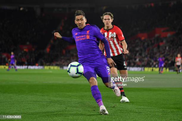 Roberto Firmino of Liverpool battles for possession with Jannik Vestergaard of Southampton during the Premier League match between Southampton FC and...