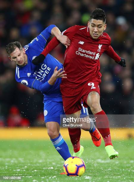 Roberto Firmino of Liverpool battles for possession with Marc Albrighton of Leicester City during the Premier League match between Liverpool FC and...