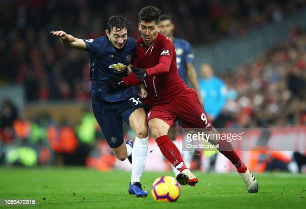 Roberto Firmino of Liverpool battles for possession with Matteo Darmian of Manchester United during the Premier League match between Liverpool FC and...