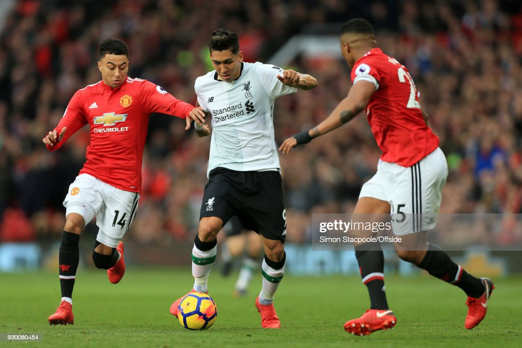 Roberto Firmino of Liverpool battles with Jesse Lingard of Man Utd (L) and Luis Antonio Valencia of Man Utd during the Premier League match between Manchester United and Liverpool at Old Trafford on March 10, 2018 in Manchester, England.