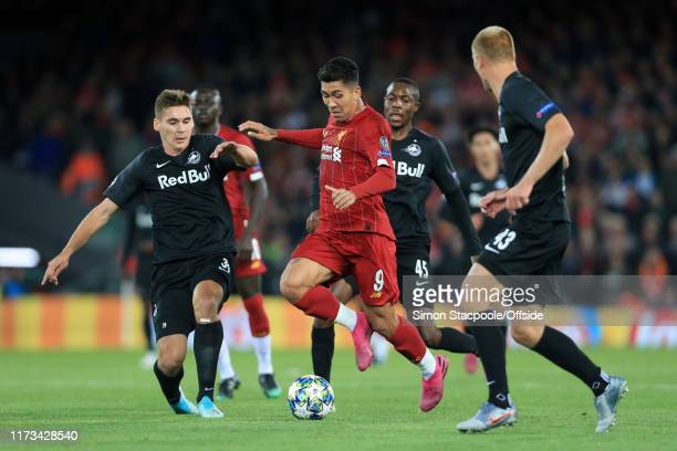 Roberto Firmino of Liverpool battles with Max Wober of Salzburg and Enock Mwepu of Salzburg during the UEFA Champions League group E match between...