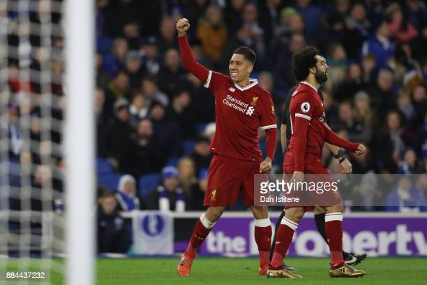 Roberto Firmino of Liverpool celebrates after scoring his sides third goal during the Premier League match between Brighton and Hove Albion and...