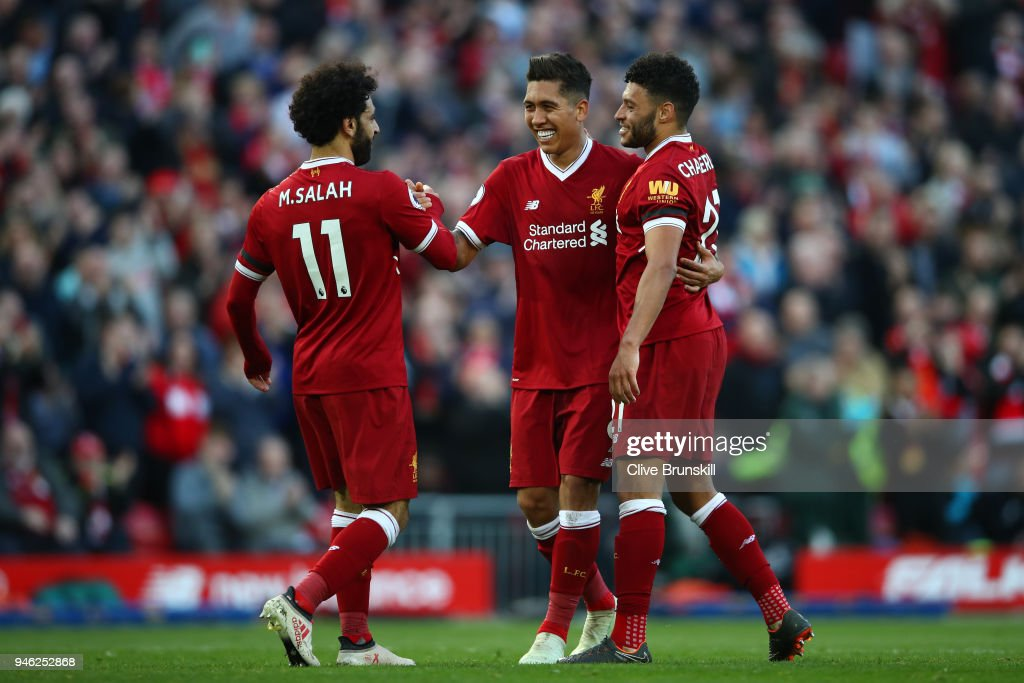 Roberto Firmino of Liverpool celebrates after scoring his sides third goal with Mohamed Salah ofLiverpool and Alex Oxlade-Chamberlain of Liverpool during the Premier League match between Liverpool and AFC Bournemouth at Anfield on April 14, 2018 in Liverpool, England.