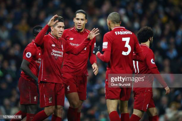 Roberto Firmino of Liverpool celebrates after scoring his team's first goal with his team mates during the Premier League match between Manchester...
