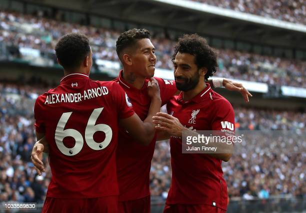 Roberto Firmino of Liverpool celebrates after scoring his team's second goal with Trent AlexanderArnold and Mohamed Salah of Liverpool during the...