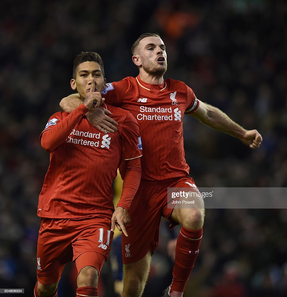 Roberto Firmino of Liverpool celebrates his second goal with Jordan Henderson of Liverpool during the Barclays Premier League match between Liverpool and Arsenal at Anfield on January 13, 2016 in Liverpool, England.