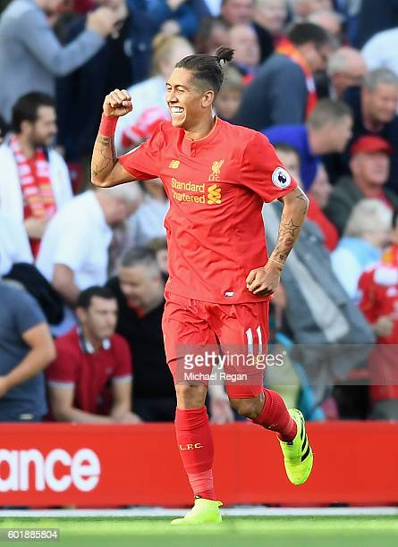 Roberto Firmino of Liverpool celebrates scoring his sides first goal during the Premier League match between Liverpool and Leicester City at Anfield...