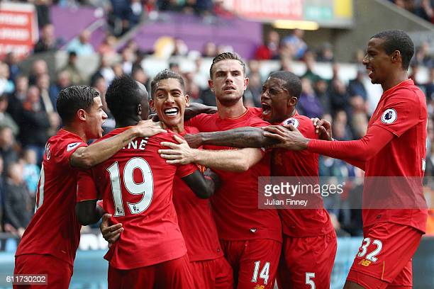 Roberto Firmino of Liverpool celebrates scoring his sides first goal with his team mates during the Premier League match between Swansea City and...