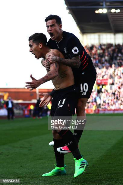 Roberto Firmino of Liverpool celebrates scoring his side's second goal with teammate Philippe Coutinho during the Premier League match between Stoke...