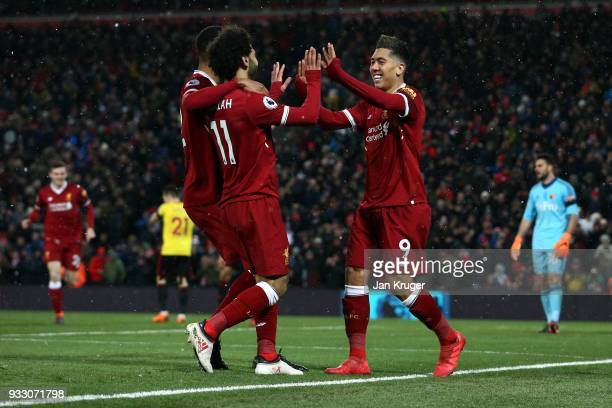 Roberto Firmino of Liverpool celebrates scoring his side's third goal with Mohamed Salah and Joe Gomez during the Premier League match between...