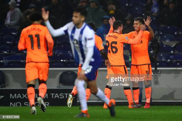 Roberto Firmino of Liverpool celebrates scoring the fourth goal with Andy Robertson during the UEFA Champions League Round of 16 First Leg match...