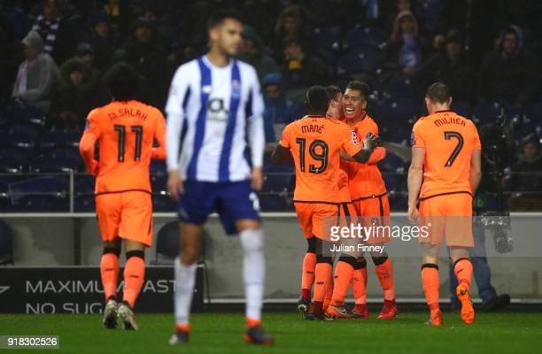 Roberto Firmino of Liverpool celebrates scoring the fourth goal with team mates during the UEFA Champions League Round of 16 First Leg match between...