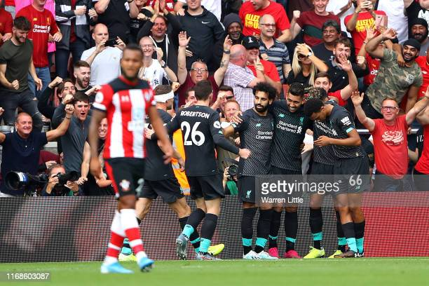 Roberto Firmino of Liverpool celebrates with his team mates after scoring their teams second goal during the Premier League match between Southampton...