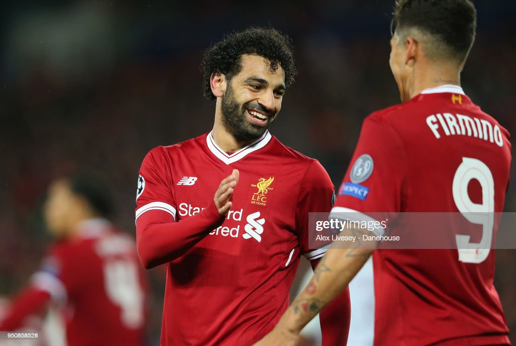 Roberto Firmino of Liverpool celebrates with Mohamed Salah after scoring their fourth goal during the UEFA Champions League Semi Final First Leg match between Liverpool and A.S. Roma at Anfield on April 24, 2018 in Liverpool, United Kingdom.