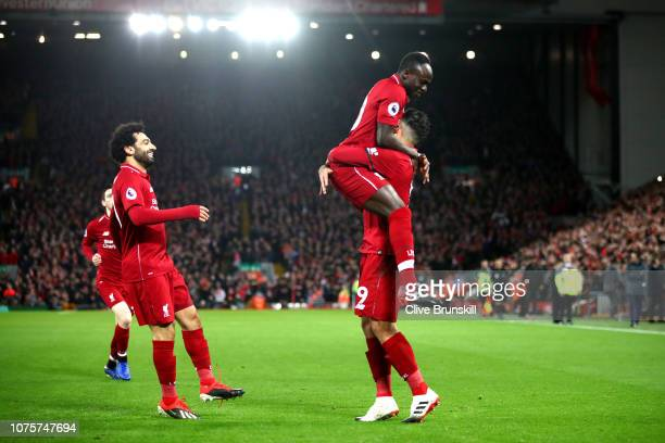 Roberto Firmino of Liverpool celebrates with Sadio Mane of Liverpool after scoring his sides first goal during the Premier League match between...