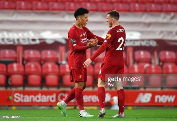 Roberto Firmino of Liverpool celebrates with team mate Andy Robertson after scoring his team's fourth goal during the Premier League match between...