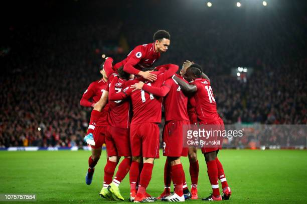 Roberto Firmino of Liverpool celebrates with team mates after scoring his sides second goal during the Premier League match between Liverpool FC and...