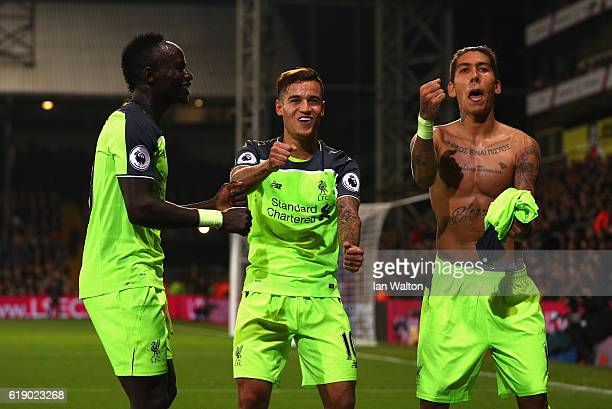 Roberto Firmino of Liverpool celebrates with team mates after scoring his team's fourth goal of the game during the Premier League match between...