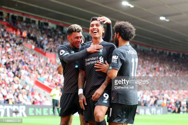 Roberto Firmino of Liverpool celebrates with team mates Alex Oxlade-Chamberlain and Mohamed Salah after scoring his team's second goal during the...