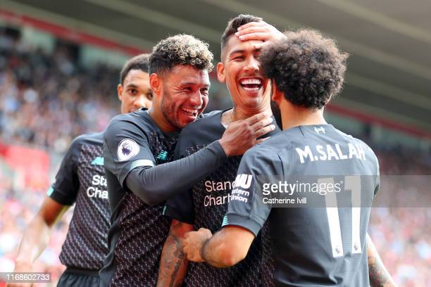 Roberto Firmino of Liverpool celebrates with team mates Alex OxladeChamberlain and Mohamed Salah after scoring his team's second goal during the...
