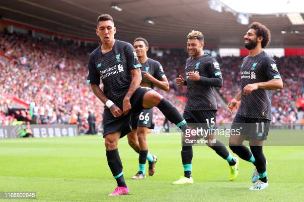 Roberto Firmino of Liverpool celebrates with team mates Mohamed Salah, Alex Oxlade-Chamberlain and Trent Alexander-Arnold after scoring his team's...