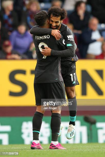 Roberto Firmino of Liverpool celebrates with teammate Mohamed Salah after scoring his team's third goal during the Premier League match between...