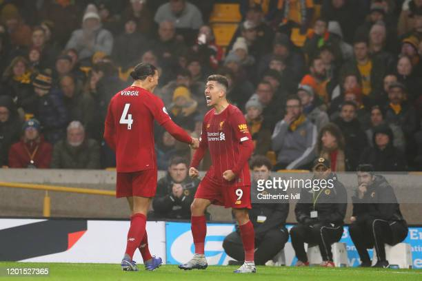 Roberto Firmino of Liverpool celebrates with teammate Virgil van Dijk after scoring their second goal during the Premier League match between...