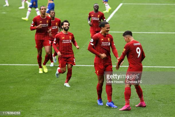 Roberto Firmino of Liverpool celebrates with teammates after scoring his team's second goal during the Premier League match between Chelsea FC and...