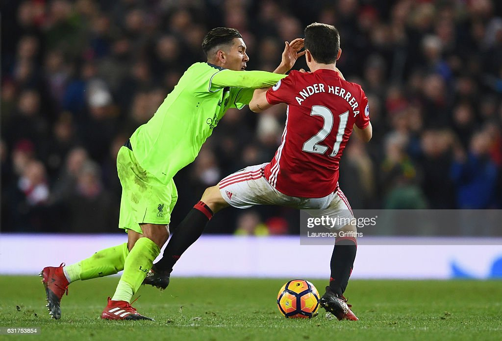 Roberto Firmino of Liverpool clashes with Ander Herrera of Manchester United during the Premier League match between Manchester United and Liverpool at Old Trafford on January 15, 2017 in Manchester, England.