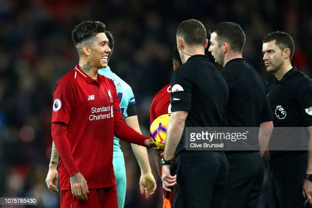 Roberto Firmino of Liverpool collects the match ball off of the officials after scoring a hattrick during the Premier League match between Liverpool...