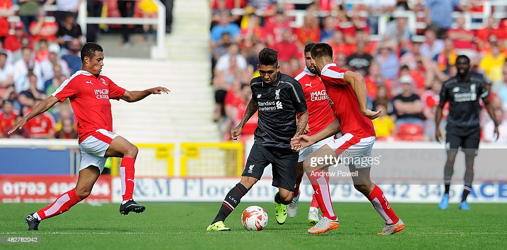 Roberto Firmino of Liverpool competes with James Dayton of Swindon Town during a pre-season friendly at County Ground on August 2, 2015 in Swindon, England.