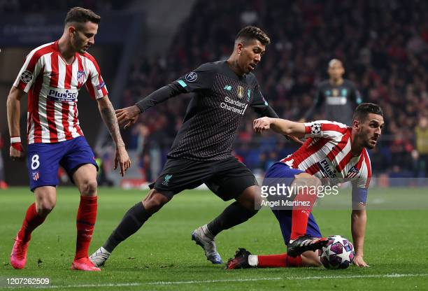 Roberto Firmino of Liverpool competes with Koke and Saul Niguez of Atletico Madrid during the UEFA Champions League round of 16 first leg match...