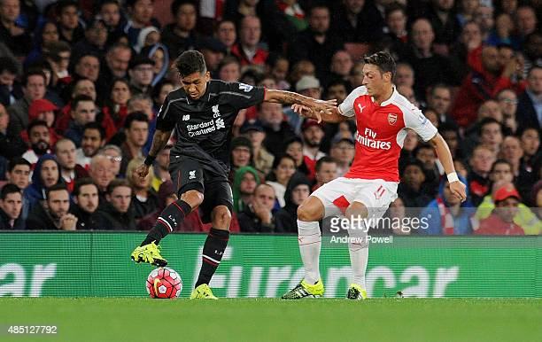 Roberto Firmino of Liverpool competes with Mesut Ozil of Arsenal during the Barclays Premier League match between Arsenal and Liverpool on August 24...