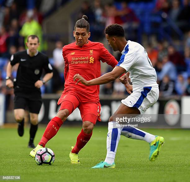 Roberto Firmino of Liverpool competes with Michael Ihiekwe of Tranmere Rovers during a PreSeason Friendly match between Tranmere Rovers and Liverpool...