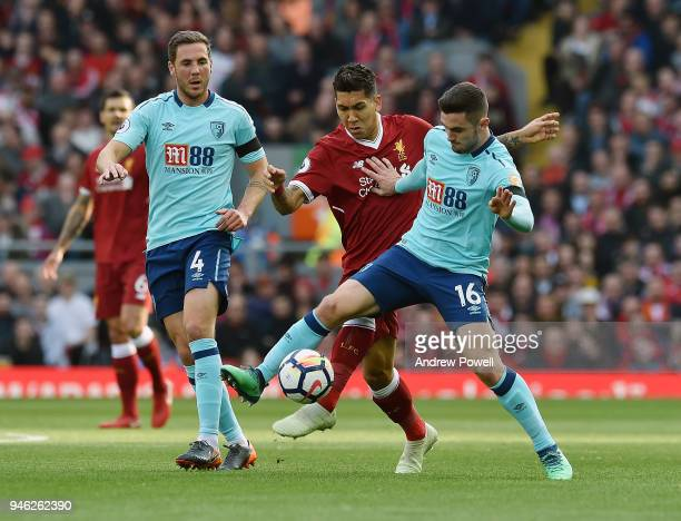 Roberto Firmino of Liverpool competes with Steve Cook and Lewis Cook AFC Bournemouth during the Premier League match between Liverpool and AFC...