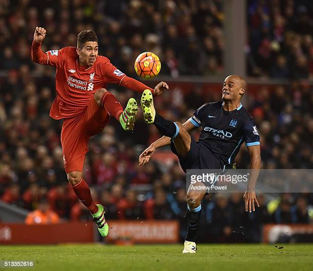 Roberto Firmino of Liverpool competes with Vincent Kompany of Manchester City during the Barclays Premier League match between Liverpool and...