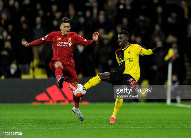 Roberto Firmino of Liverpool competing with Ismaila Sarr of Watford during the Premier League match between Watford FC and Liverpool FC at Vicarage...