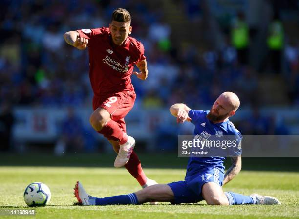 Roberto Firmino of Liverpool evades Aron Gunnarsson of Cardiff City during the Premier League match between Cardiff City and Liverpool FC at Cardiff...