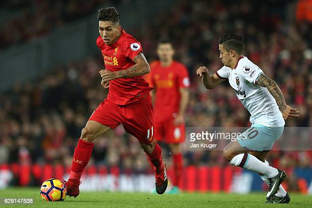 Roberto Firmino of Liverpool evades Manuel Lanzini of West Ham United during the Premier League match between Liverpool and West Ham United at...