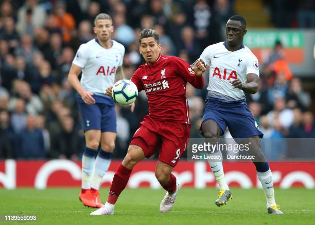 Roberto Firmino of Liverpool FC is tackled by Davinson Sanchez of Tottenham Hotspur during the Premier League match between Liverpool FC and...