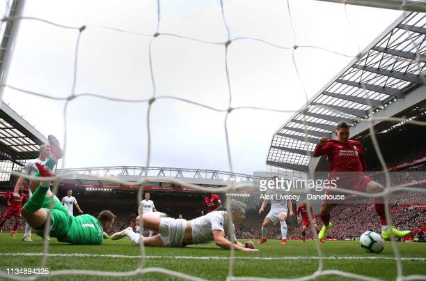 Roberto Firmino of Liverpool FC scores his goal during the Premier League match between Liverpool FC and Burnley FC at Anfield on March 10 2019 in...