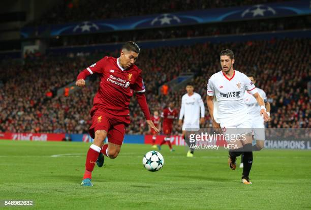 Roberto Firmino of Liverpool FC shoots past Sergio Escudero of Sevilla FC during the UEFA Champions League group E match between Liverpool FC and...