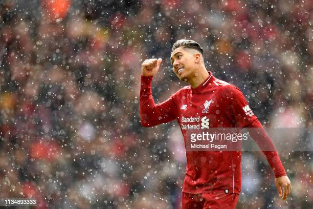 Roberto Firmino of Liverpool gestures as sleet falls during the Premier League match between Liverpool FC and Burnley FC at Anfield on March 10 2019...