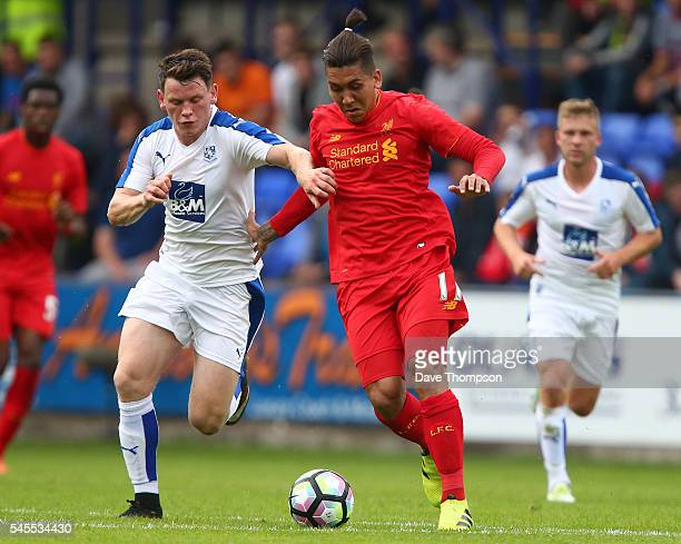 Roberto Firmino of Liverpool gets past Connor Jennings of Tranmere Rovers during the PreSeason Friendly match between Tranmere Rovers and Liverpool...