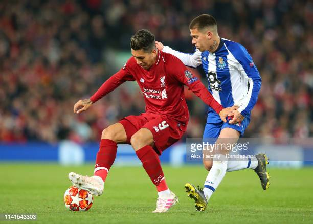 Roberto Firmino of Liverpool holds off a challenge from Otavio of Porto during the UEFA Champions League Quarter Final first leg match between...